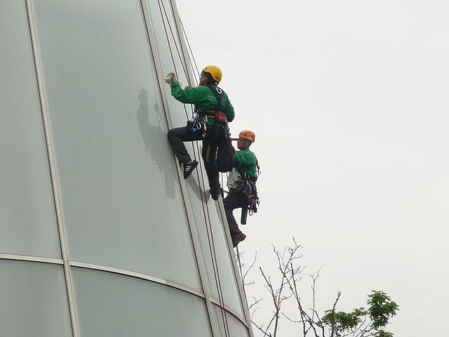 Промышленные альпинисты на фасаде здания